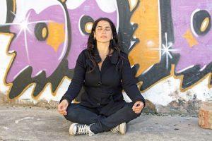 women meditating in front of inner city graffiti mural