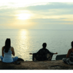 three people meditating on rocks with expansive ocean view