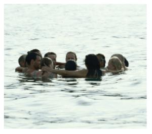 circle of people arm in arm immersed in ocean water