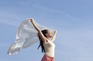 woman holding scarf above head in wind