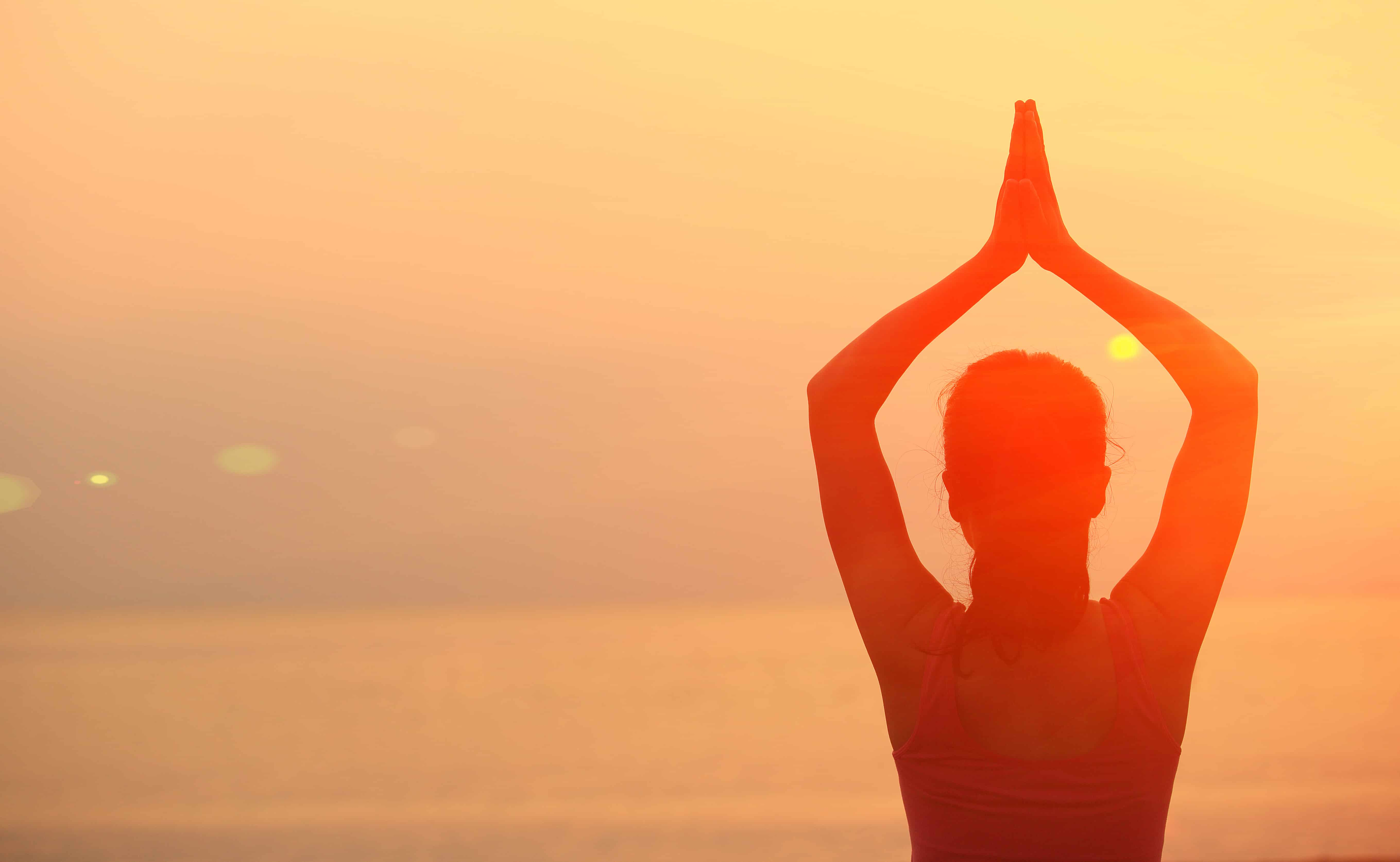 yoga woman in orange sunset on the water