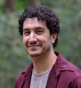 Man with curly hair, red shirt.